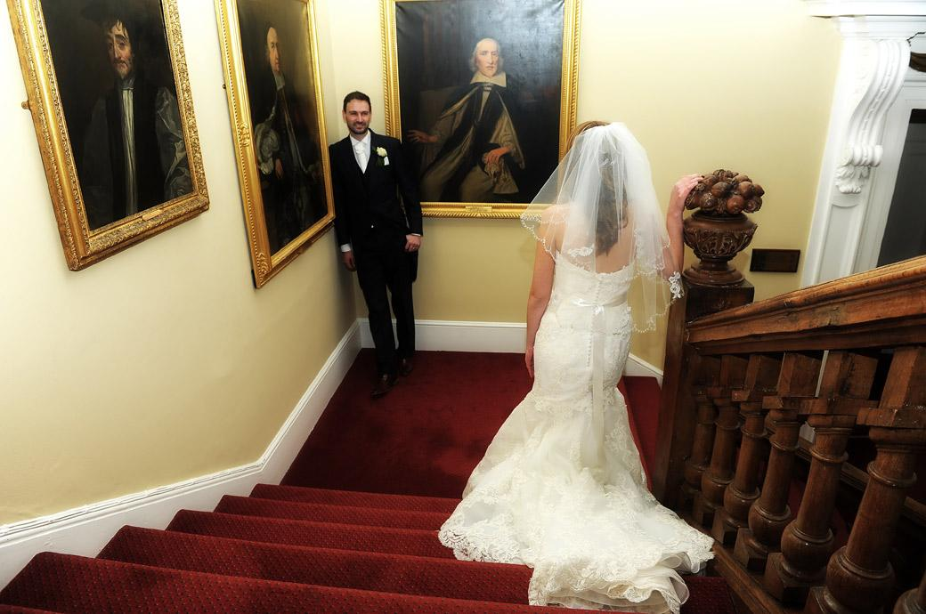 Bride on the stairs looks down to her husband standing by pictures of Winchester Bishops waiting for her in this fun wedding photograph taken at Surrey wedding venue Farnham Castle