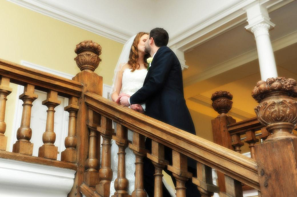 The Bride and Groom romantically kiss on the wooden staircase in this wedding photo taken at the wonderful Farnham Castle by Surrey Lane wedding photography