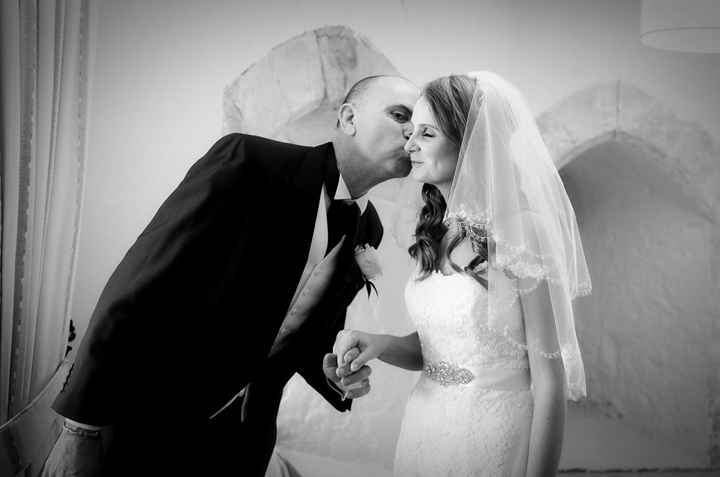 Father of the Bride offers a loving kiss in this sweet wedding photograph captured in the Stone Hall before entering The Lantern Hall at Farnham Castle a unique Surrey wedding venue