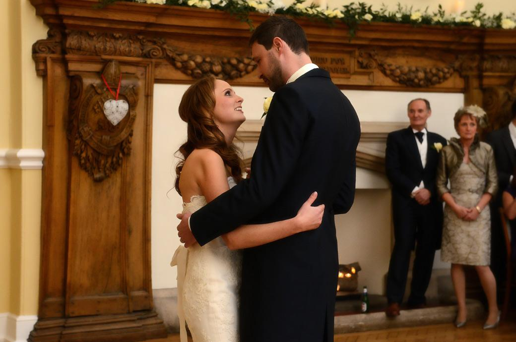 Close up wedding photograph of a loving look during the newly-wed's first dance captured in front of the magificent fireplace in The Great Hall at Farnham Castle in Surrey