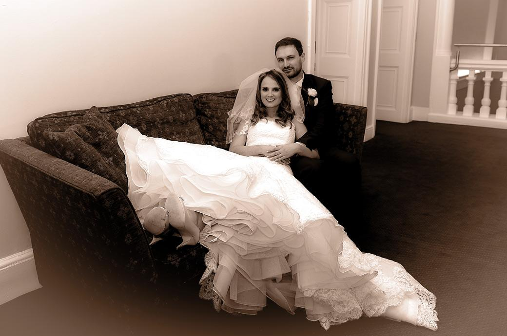 Smiling Bride sitting in her wonderful dress with her husband on a sofa in this wedding photograph taken on the second floor of Surrey wedding venue Farnham Castle