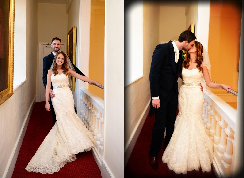 Leaning on the balustrade and kissing in these two care free wedding wedding photographs taken on the balcony overlooking The Great Hall at Surrey wedding venue Farnham Castle