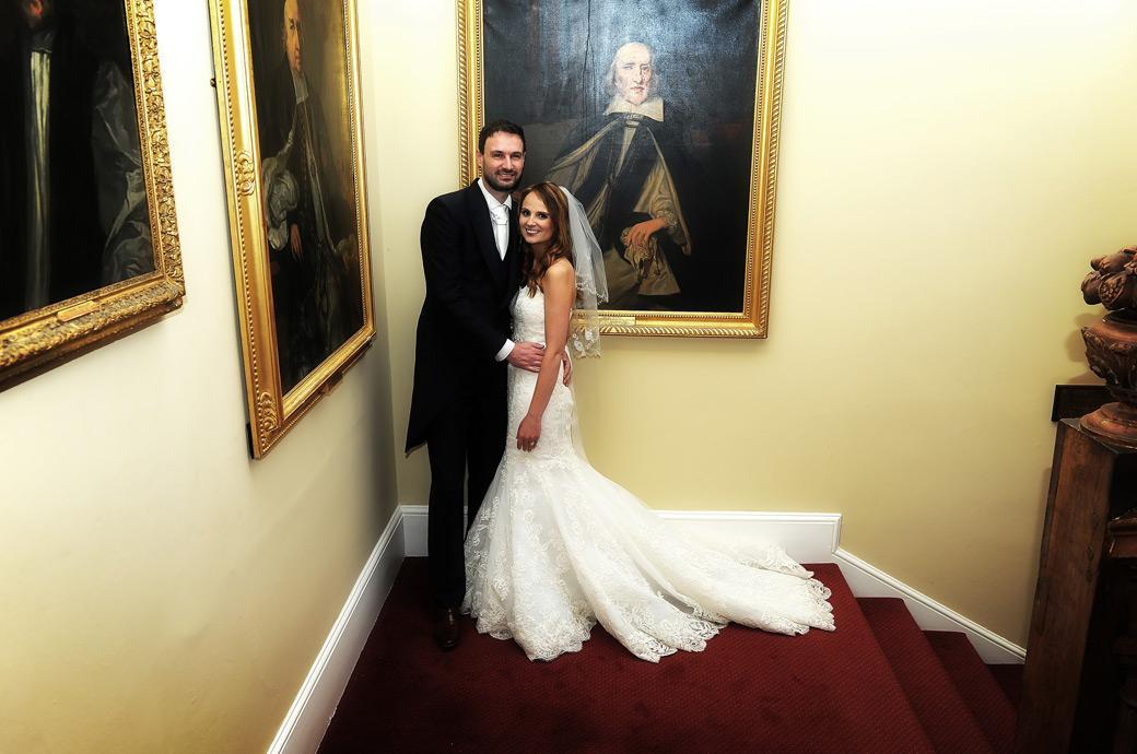 Smiling newly-wed couple pose for their Surrey Lane wedding photographer in a wedding photo taken on the stairs at Farnham Castle inbetween pictures of the Bishops of Winchester