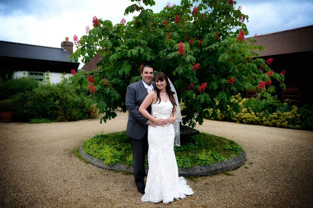 All smiles for the newly-weds in this pretty wedding picture taken in front of a flowering ornamental tree in the little rustic garden of Surrey wedding venue Gate Street Barn