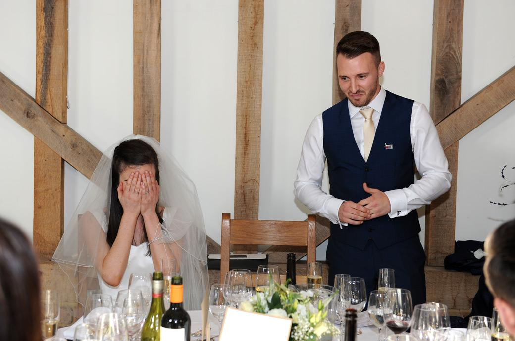 Amusing wedding photo of the Bride covering her face as the groom reveals a funny story during the speeches at Surrey wedding venue Gate Street Barn in Bramley Guildford