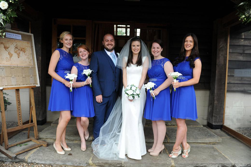 Fun and unusual wedding photograph of the Bride posing with her Bridesmaids and a Brides man on the steps of Gate Street Barn a delightful wedding venue in Bramley Surrey