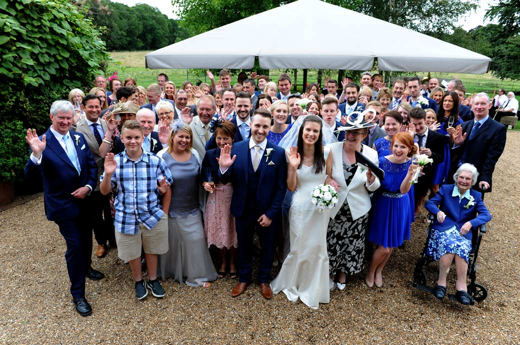 Newlyweds with their guests at Gate Street Barn in Bramley waving at the Surrey Lane wedding photographer for the fun and relaxed everyone at the wedding photograph