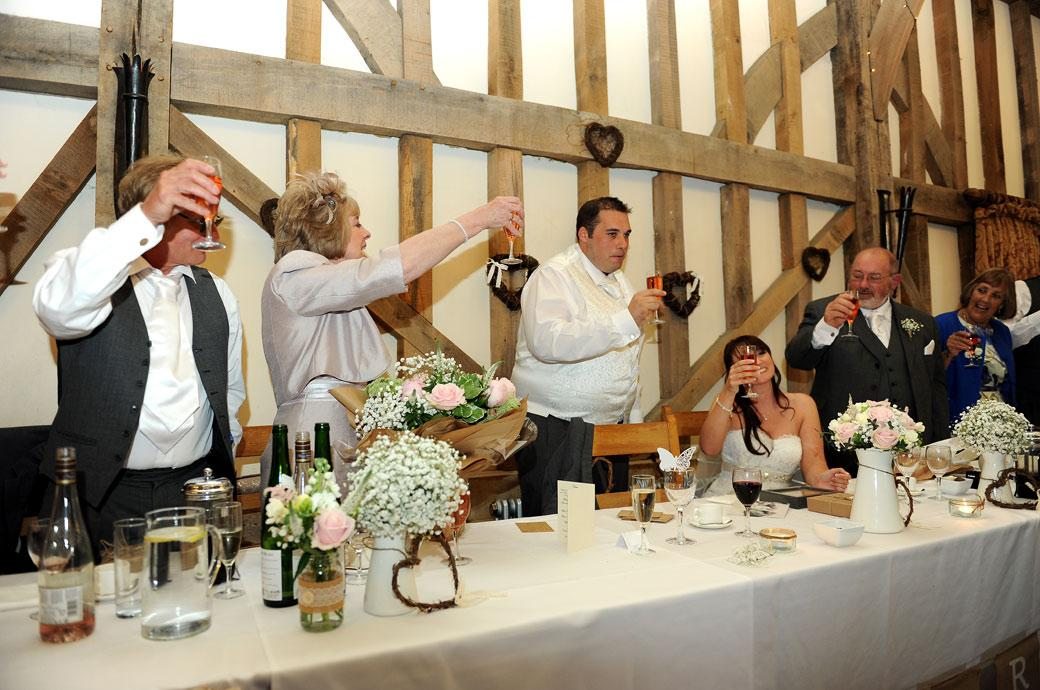 Head table ends the toasts with a final raising of glasses for the beautiful new Bride in this happy wedding photograph captured at Gate Street Barn by Surrey Lane wedding photography