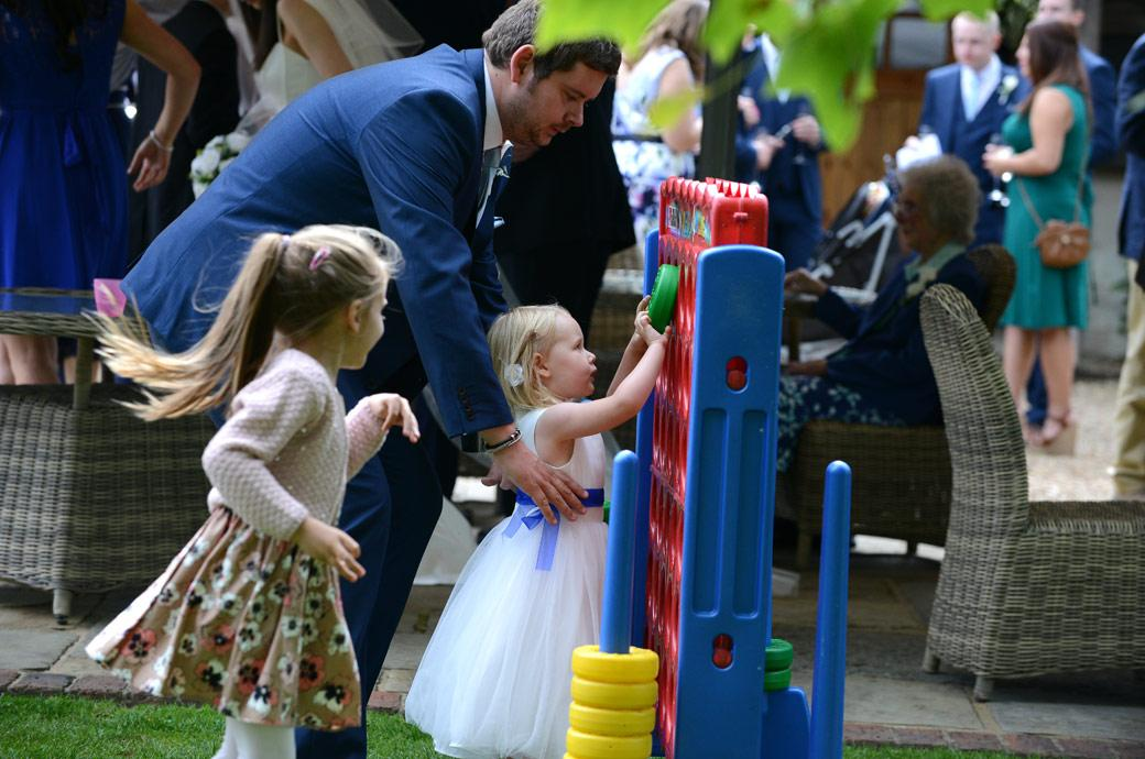 A small flower girl being helped up by her dad at Surrey wedding venue Gate Street Barn to play the giant connect game in the garden during the wedding reception