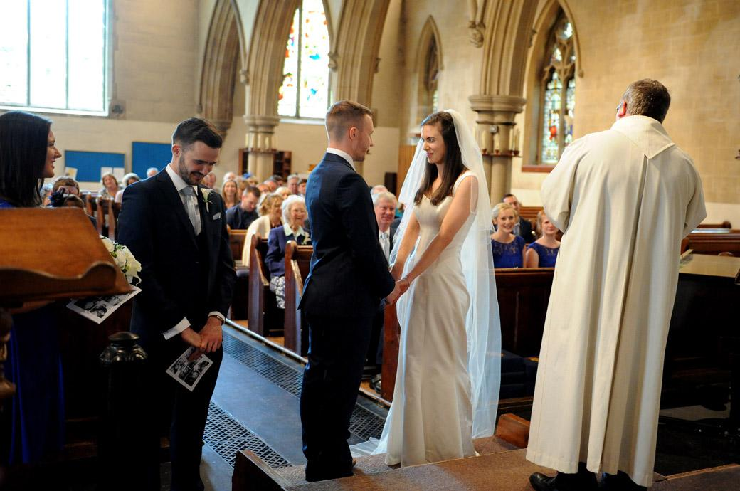 Bride and Groom face each other and hold hands as they say their marriage vows in the church before leaving for Gate Street Barn in Surrey for their wedding reception