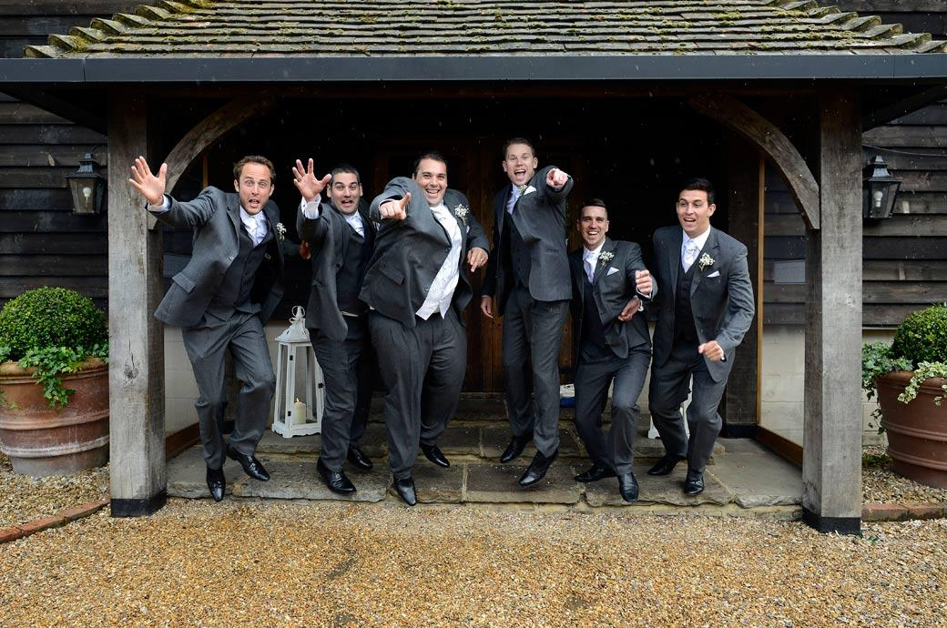 Groom and Groomsmen caught jumping in the air in this funny wedding picture taken at the renowned and very in demand Surrey wedding venue Gate Street Barn near Guildford