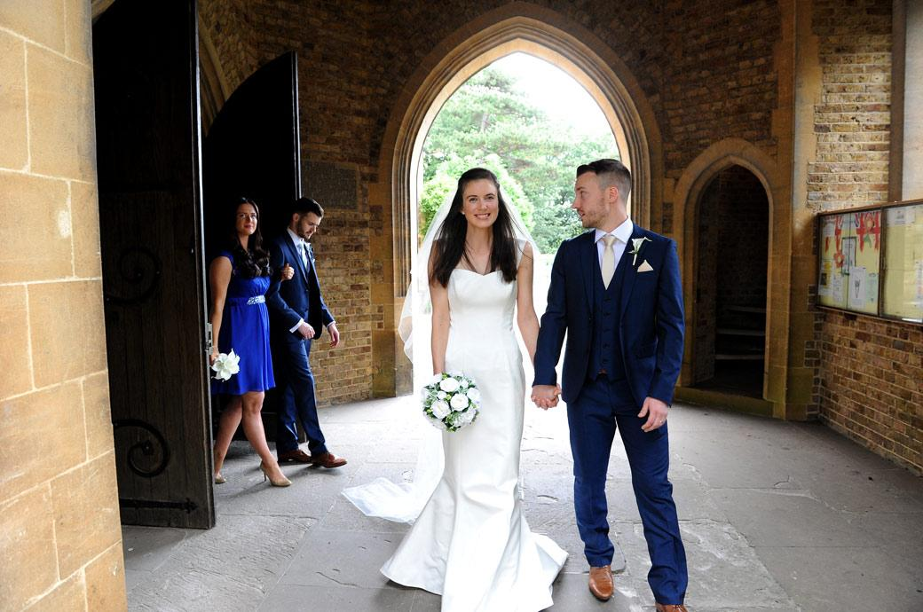 An overjoyed beautiful Bride looks radiant as she leaves the church with her husband captured by a Surrey Lane wedding photographer going onto a Gate Street Barn reception