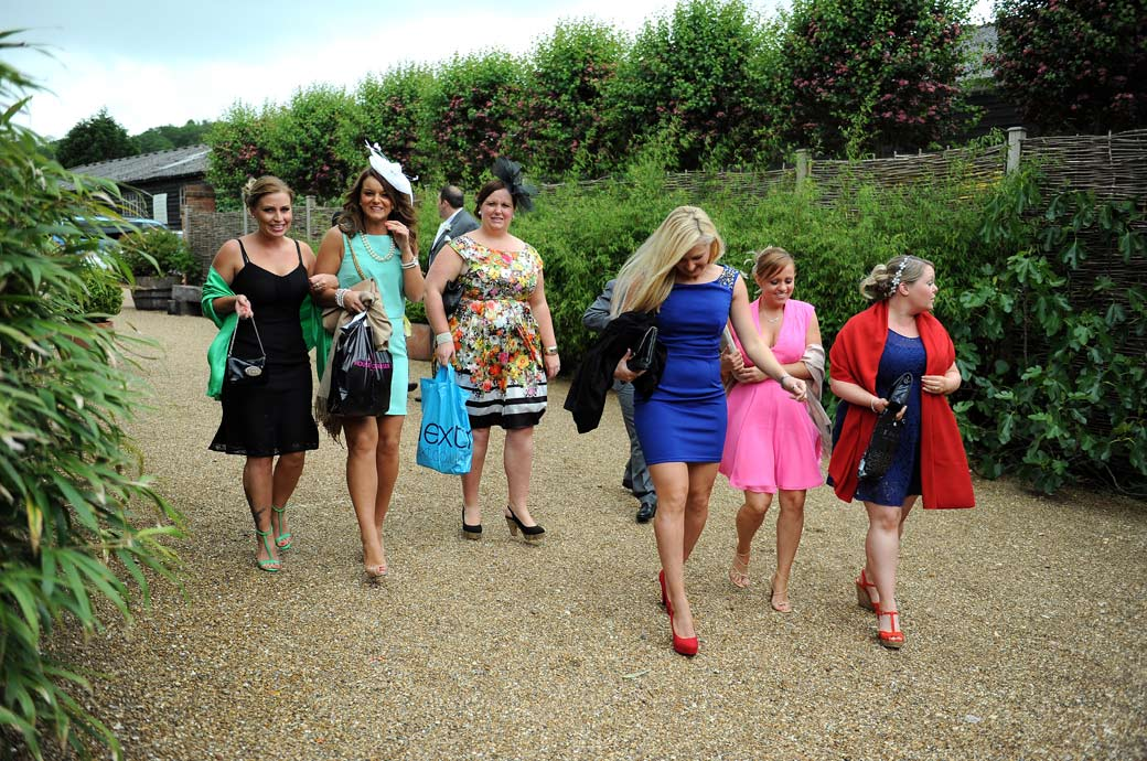Ladies in various bright coloured summer dresses arriving at the delightful Gate Street Barn in this informal wedding picture captured by Surrey Lane wedding photography