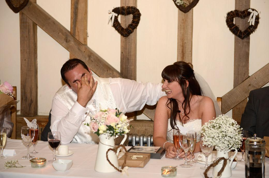Bride and Groom in a state of uncontrollable laughter in this fun wedding picture taken during the Best man's speech in Surrey wedding venue Gate Street Barn