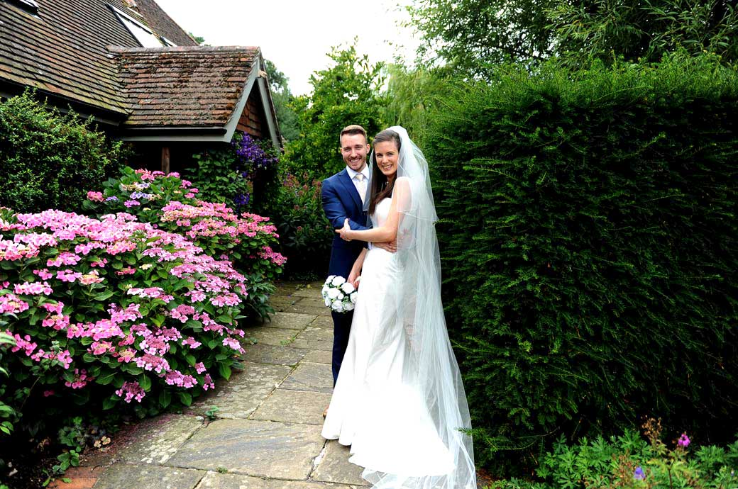 Laughing Bride and groom in this wedding photograph share a joke in the colourful garden at Gate Street Barn a delightful Surrey wedding venue in Bramley Guildford