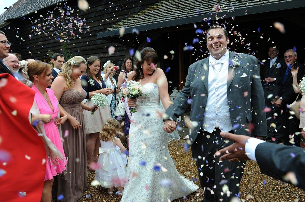 The confetti keeps falling on the happy Bride and Groom in this wedding photo taken on the gravel outside the front door of Gate Street Barn near Guildford in Surrey