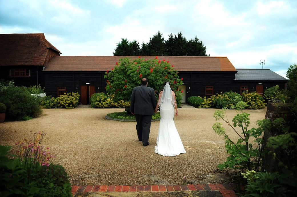 Back view wedding picture of the newly-wed couple walking towards through the pretty garden at the lovely Gate Street Barn near Guildford Surrey