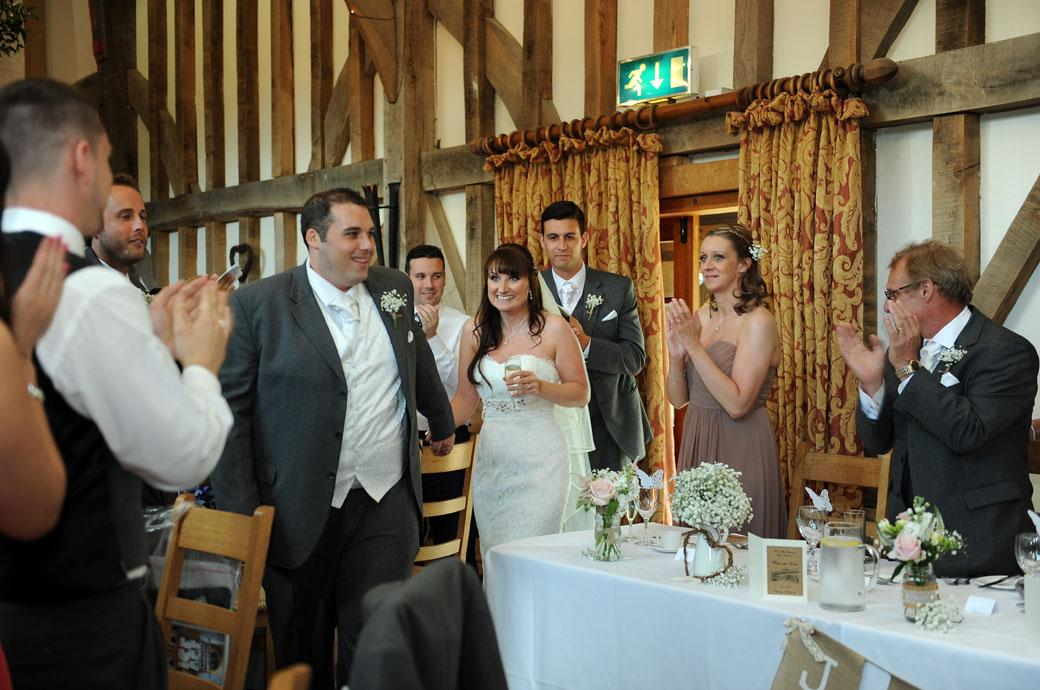 The excited Bride and Groom come in for the wedding breakfast to rapturous applause at the magical Surrey wedding venue Gate Street Barn in Bramley near Guildford
