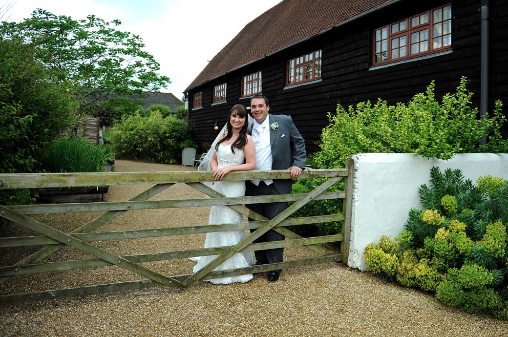 A very happy Bride and Groom pose by the farm gate in this relaxed wedding picture taken by Surrey Lane wedding photography at the rustic and idyllic Gate Street Barn