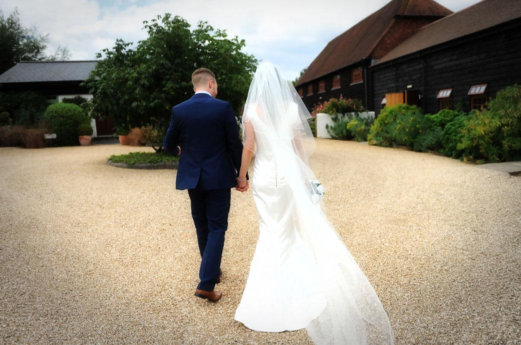 Bride and groom walking hand in hand across the gravel to see the wedding breakfast settings  at Surrey wedding venue Gate Street Barn in Bramley village