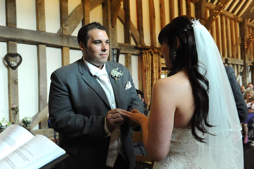 Groom fixes his eyes on this Bride as he places the wedding ring on her finger in the atmospheric wedding picture taken in Bramley Surrey at the beautiful Gate Street Barn