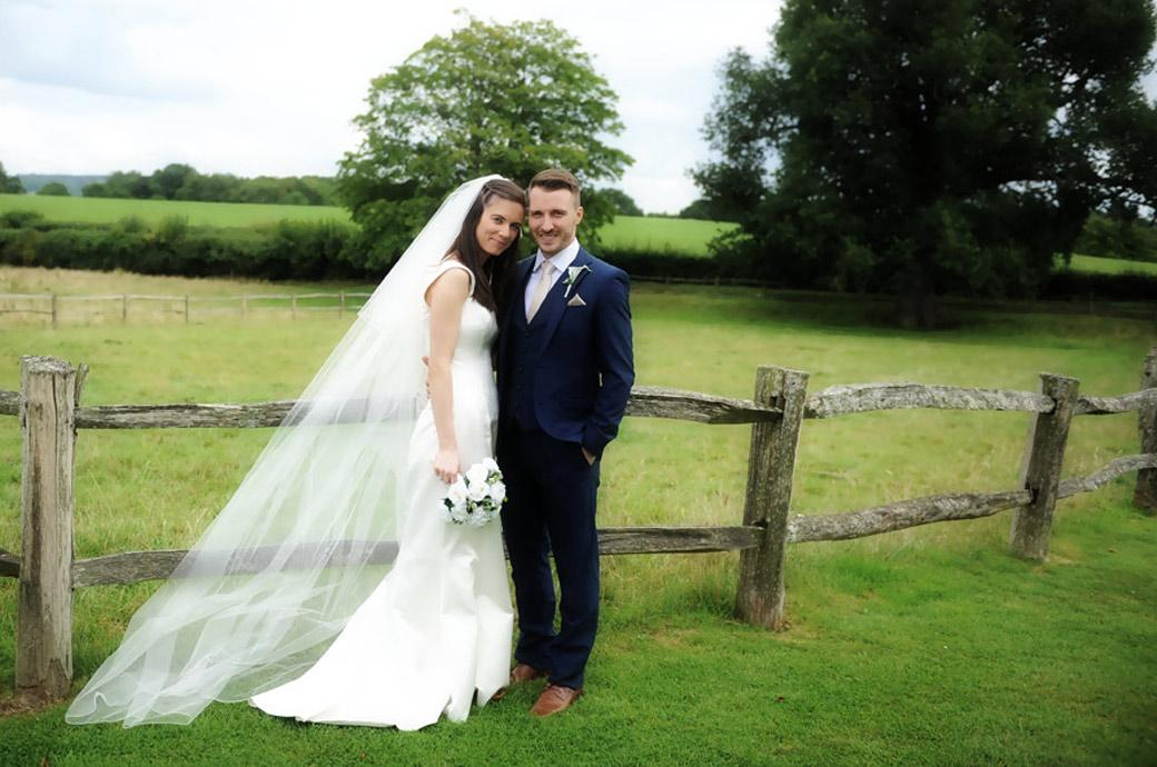 Handsome newlywed couple relax  in front of the lovely green fields at the pretty and rural Gate Street Barn a delightful wedding venue in the village of Bramley Surrey