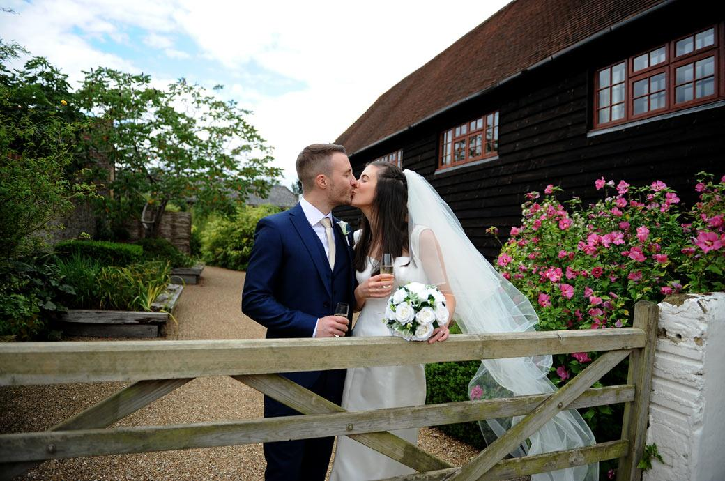 Bride and Groom kiss in this romantic wedding picture taken at Surrey wedding and reception venue Gate Street Barn by a wooden farm gate in the yard at the front