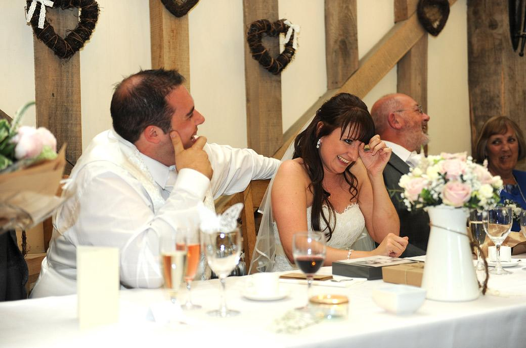 The Bride wipes tear of laughter from her eyes in this funny wedding photo taken during the Best Man's speech at the lovely Gate Street Barn in Guildford Surrey