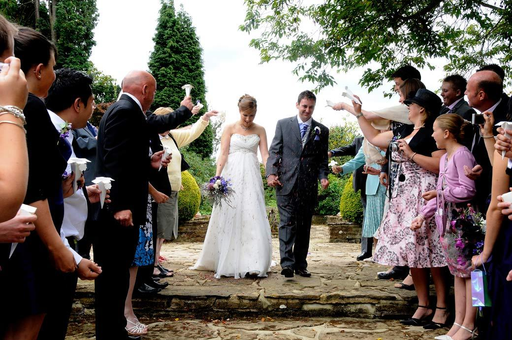 Bride and Groom captured in the wedding picture as they near the end of the line of confetti throwers on the patio steps at Gatton Manor a popular Surrey wedding venue