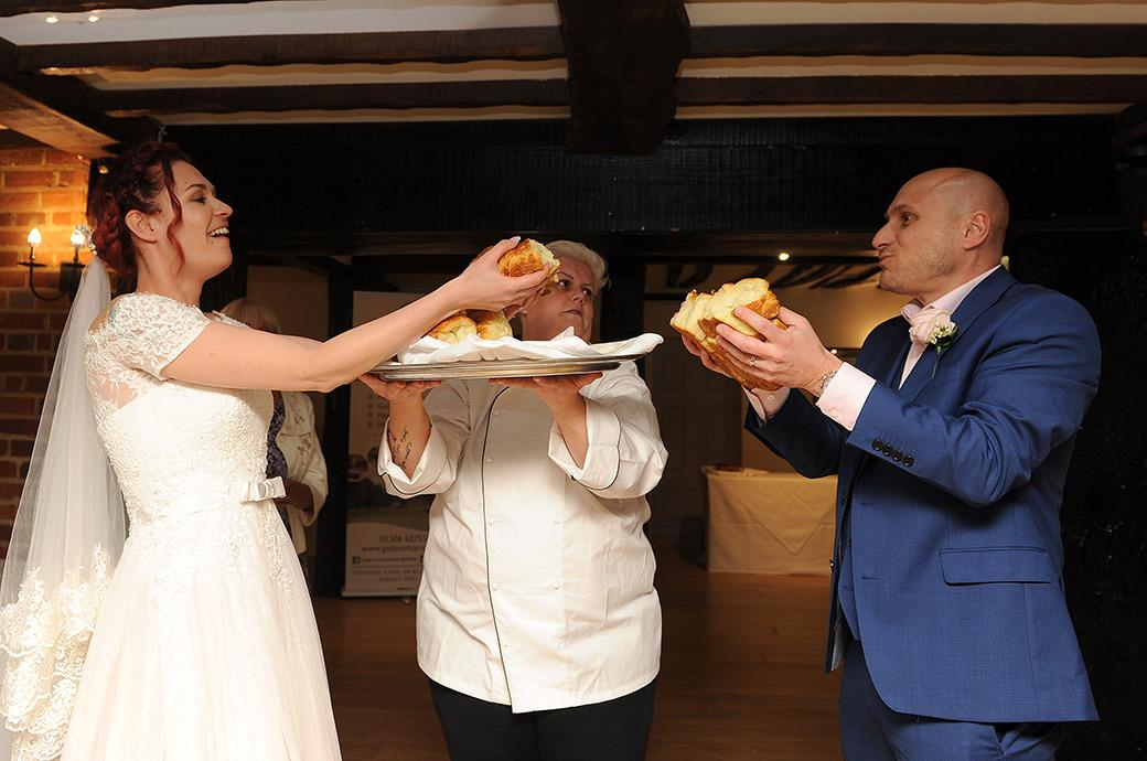 Wedding picture of the Bulgarian wedding tradition of breaking the large loaf of bread by the Bride and groom captured at Surrey  venue Gatton Manor in Dorking