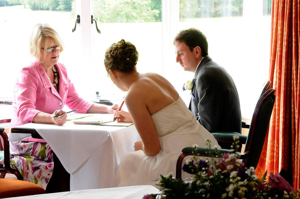 Bride signing the marriage register in this relaxed wedding photo taken in the Abinger Room at Gatton Manor a fine wedding venue nr Dorking in Surrey