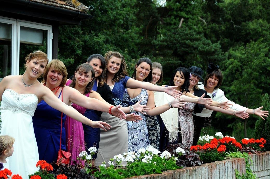 Happy Bride with her ladies holding out their arms as they celebrate during the wedding reception at Surrey wedding venue Gatton Manor out on the terrace