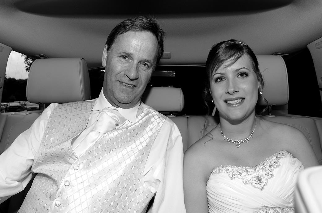 Smiling Bride with her father captured in this wedding photograph as they sit in the back of the bridal car on arrival at Gatton Manor a fine Surrey wedding venue