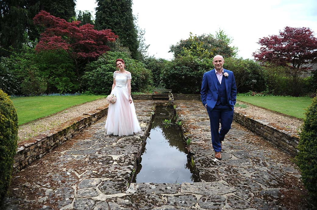 Happy bride and groom walk nonchalantly alongside the Victorian pond and fountain during their walk around the grounds of Gatton Manor in Dorking Surrey
