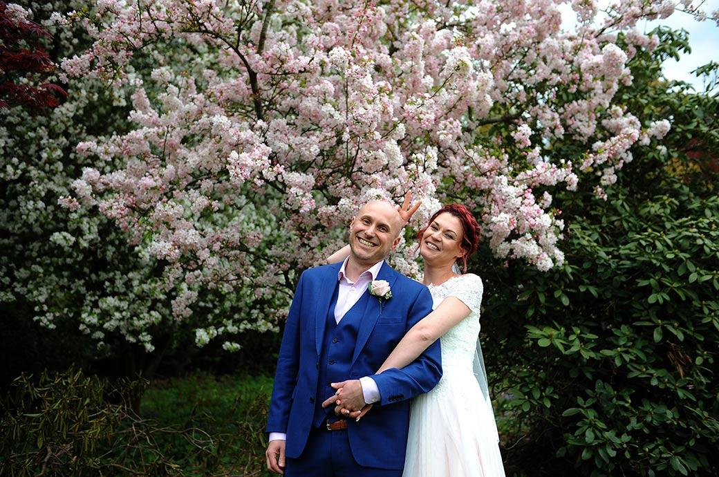 Wedding picture of a Bride and Groom all smiles as they have fun in front of some lovely pink blossom during their walk at Gatton Manor in Dorking Surrey