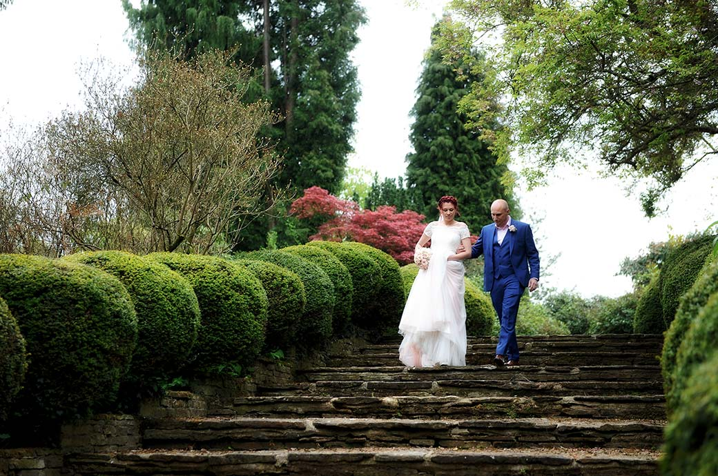 Bride and groom dressed in light pink and bright blue respectively captured walking down the stone steps at the Surrey wedding venue Gatton Manor