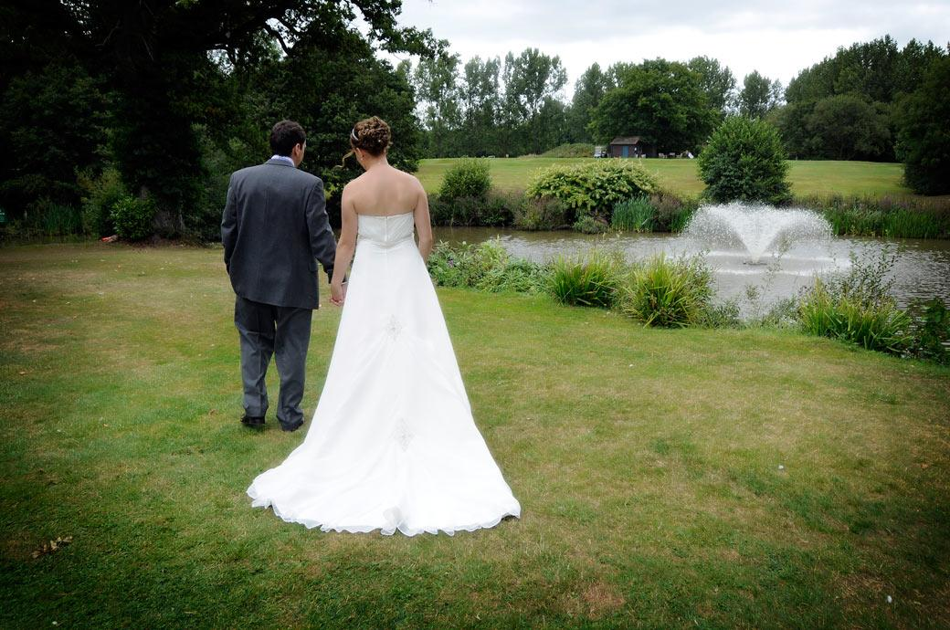 Romantically walking hand in hand towards the lake the newlywed couple captured in this wedding photo as they talk a walk around the tranquil Gatton Manor in Dorking Surrey