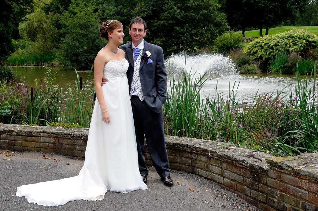 A content Groom wedding photo as he stands with his new wife with the fountain in the background near the lake at Gatton Manor Surrey wedding venue