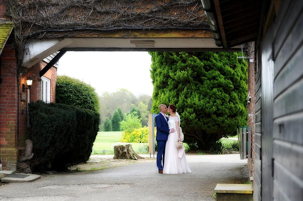 Romantic moment captured in this wedding photograph taken at Surrey wedding venue Gatton Manor as the Bride and groom kiss under the arch of the main building