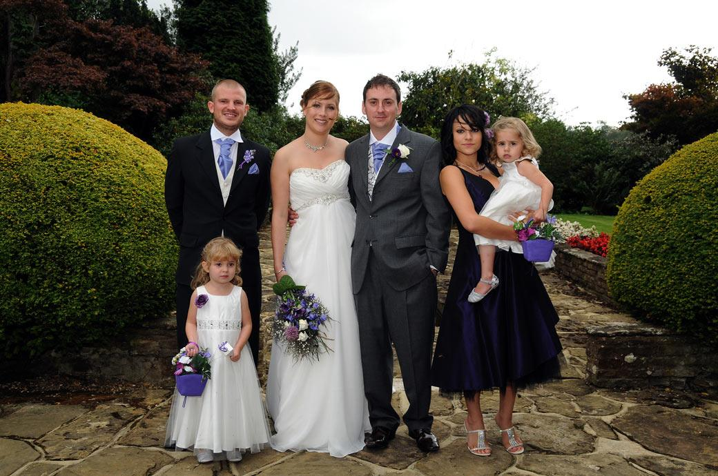 Relaxed intimate wedding photograph of the Bride and Groom with their Best man and Bridesmaid  taken at a Gatton Manor Surrey wedding on the extensive patio