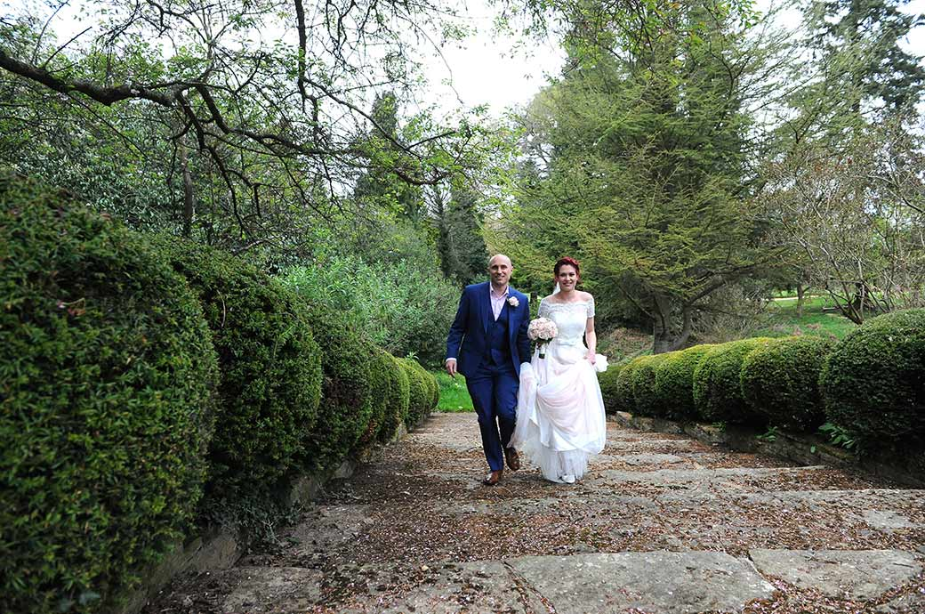 Smiling newlyweds at Surrey wedding venue Gatton Manor in Dorking Surrey walk together up the bud covered stone flag stone steps in the Victorian Garden