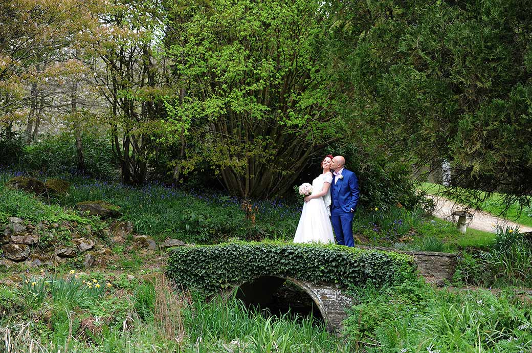 Relaxed and romantic wedding kiss captured at popular Surrey venue Gatton Manor on one of the many small ivy covered bridges found in the old Victorian gardens