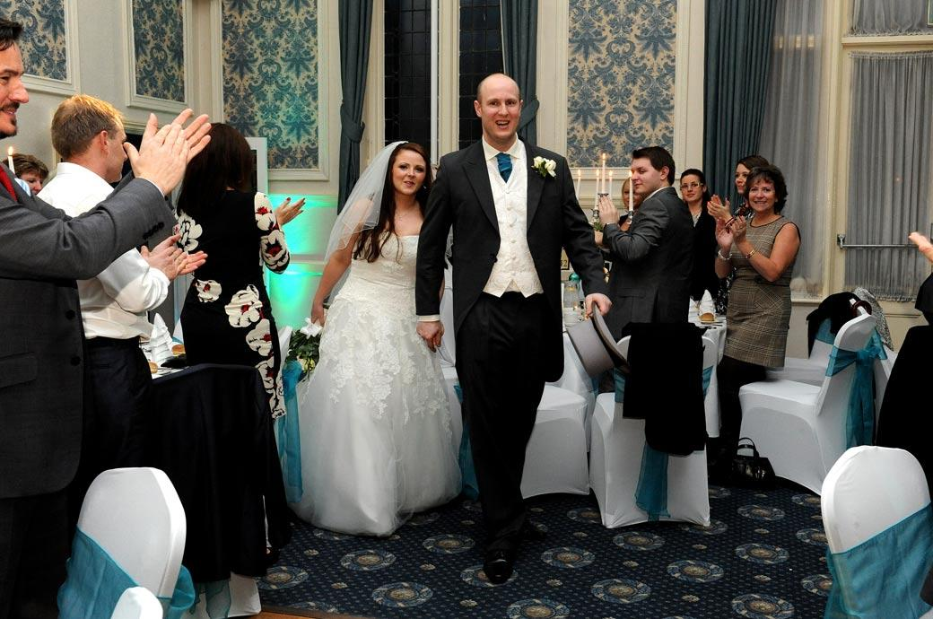 Bride and Groom entering the dining room to much applause wedding picture captured in the Elizabethan Suite at Glenmore House Surrey