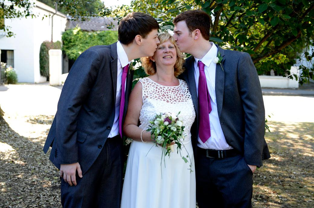 Fun and  relaxed wedding photograph of the Bride being kissed by her two sons in Crescent Gardens opposite Surrey wedding venue Glenmore House