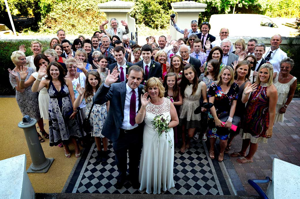 Everyone waving from the front steps of  Glenmore House in this relaxed fun wedding picture taken by Surrey Lane wedding photographers