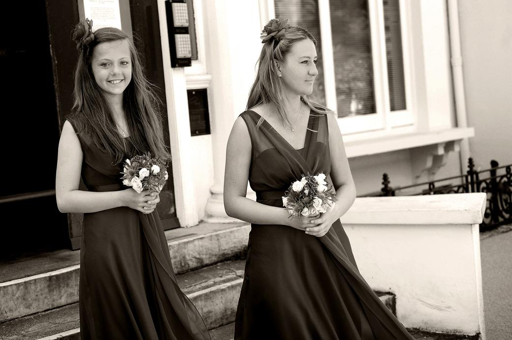 Two sweet Bridesmaids captured by Surrey Lane wedding photographers in this wedding photograph taken as they wait at the front door of  Glenmore House