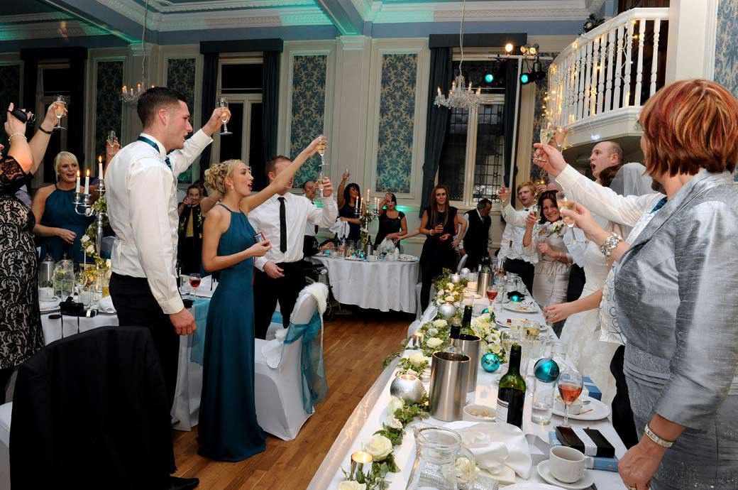 An everyone happily and loudly toasting the Bride and Groom wedding photo captured by Surrey Lane wedding photography at Glenmore House