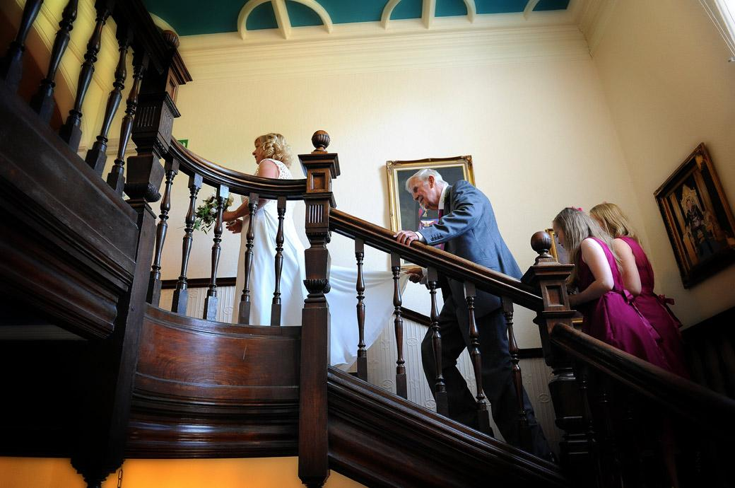 Father holds the Bride's dress followed by the Bridesmaids on the staircase in this sweet wedding photo taken at Surrey wedding venue  Glenmore House