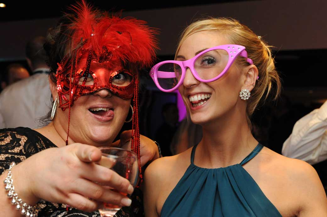 Eye-catching guests in a colourful fancy dress wedding photo ready for the photo booth in the Onslow bar at Glenmore House Surrey wedding venue