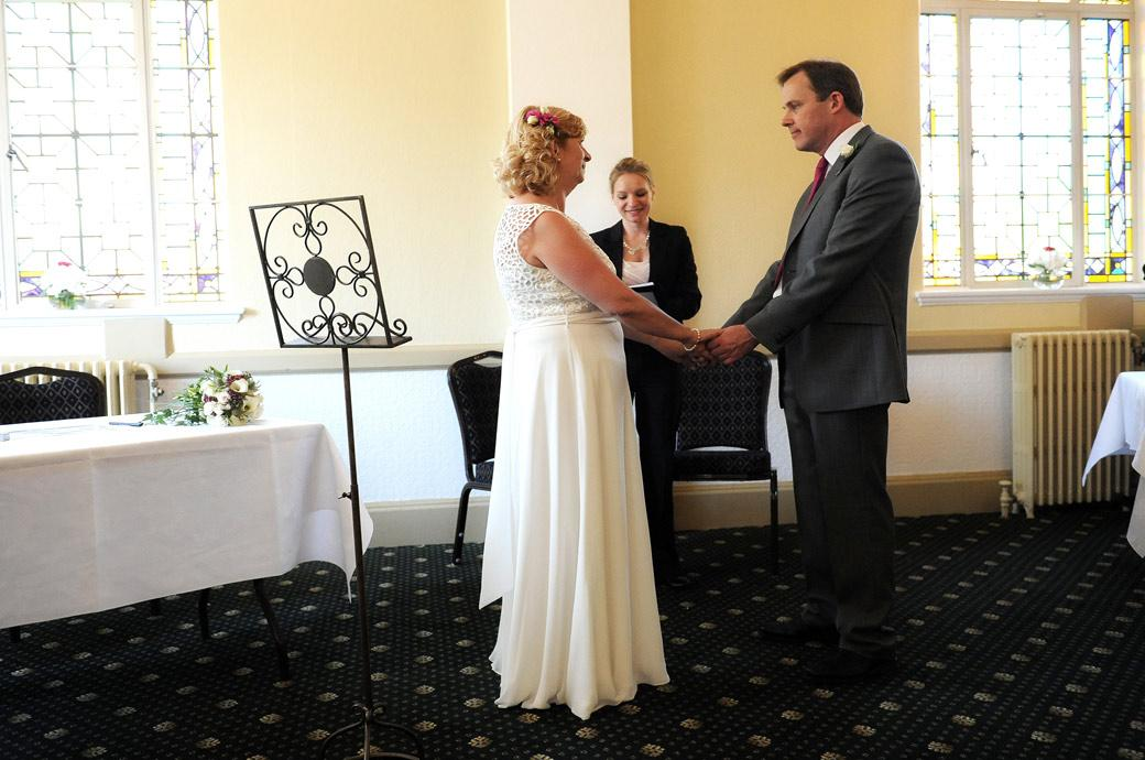 Wedding photo of the Bride and Groom holding hands during the ceremony in the Tudor Room at Glenmore House by Surrey Lane wedding photographers